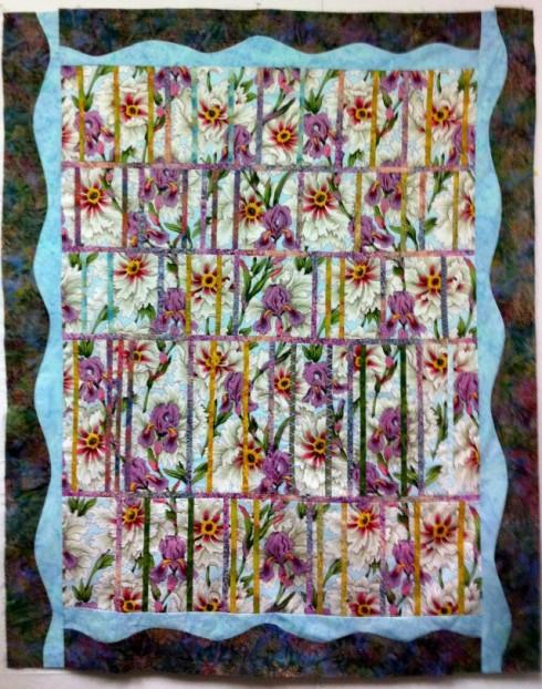 Lovely Irises peek through the jalousie in this quilt