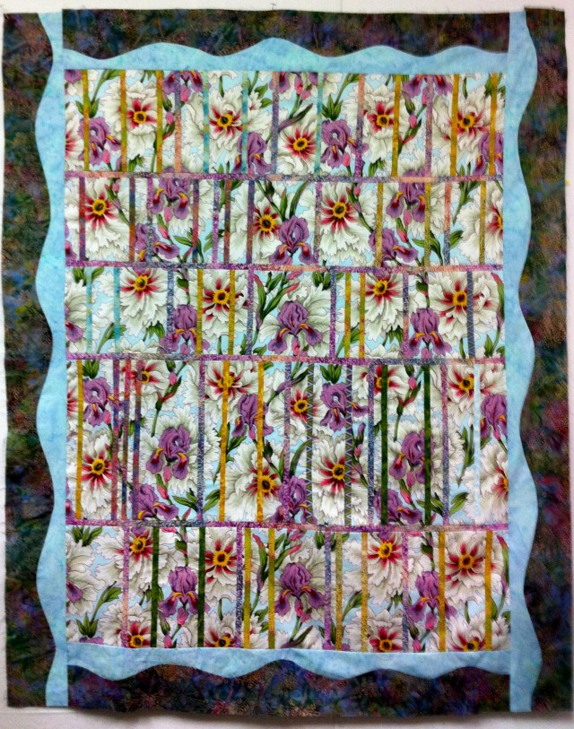 Lovely Irises peek through the jalousie in this quilt