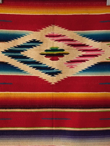 Serape blanket with white triangles in diamond shape